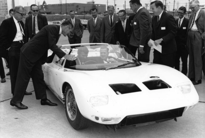 Carroll Shelby (seated, left) and Henry Ford II (seated, right) in a 1965 GT40 108 Roadster.