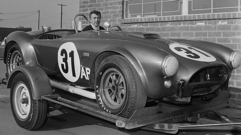 Carroll Shelby sitting in a Shelby Cobra.