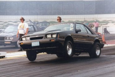 Black foxbody mustang launching at drag strip