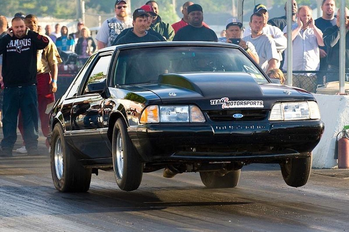 Foxbody Mustang launching at drag strip
